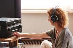 Πιέζοντας κουμπί γυναικών στο ηχητικό σύστημα που φορά τα ακουστικά Στοκ Εικόνες