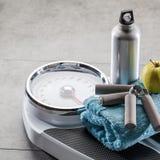 Πιασίματα χεριών, φιάλη αλουμινίου και μήλο στο πάτωμα γυμναστικής, copyspace στοκ εικόνα