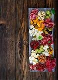 Πιατέλα τομέα εστιάσεως Antipasto με το μπέϊκον, jerky, το λουκάνικο, το μπλε τυρί και τα σταφύλια Στοκ Φωτογραφία