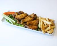 Πιατέλα των φτερών και των τηγανιτών πατατών κοτόπουλου στοκ φωτογραφίες