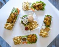 Πιατέλες των φτερών, cheeseburgers, και των τηγανιτών πατατών κοτόπουλου στοκ εικόνα