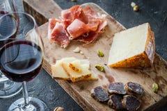 Πιατέλα με το ισπανικό serrano ζαμπόν jamon ή toscano pecorino το ιταλικό crudo prosciutto, τεμαχισμένο ιταλικό σκληρών τυριών Στοκ φωτογραφίες με δικαίωμα ελεύθερης χρήσης