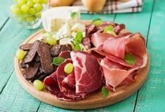 Πιατέλα τομέα εστιάσεως Antipasto με το μπέϊκον, jerky, το λουκάνικο, το μπλε τυρί και τα σταφύλια Στοκ Εικόνα