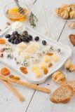 Πιατέλα τυριών με τα διαφορετικά φρούτα και τα καρύδια στην άσπρη ξύλινη επιτραπέζια κατακόρυφο Στοκ Εικόνα