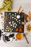 Πιατέλα τυριών με τη διαφορετική τοπ άποψη φρούτων και καρυδιών Στοκ Εικόνες