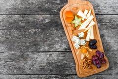 Πιατέλα τυριών που διακοσμείται με το αχλάδι, μέλι, ξύλα καρυδιάς, σταφύλια, carambola, physalis στον τέμνοντα πίνακα στο ξύλινο  Στοκ εικόνες με δικαίωμα ελεύθερης χρήσης
