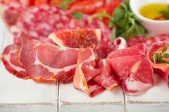 Πιατέλα Antipasti του θεραπευμένου κρέατος, jamon, λουκάνικο, salame στο whi Στοκ Φωτογραφίες
