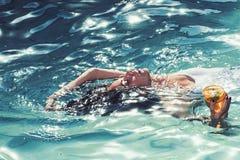 Πιείτε το κοκτέιλ κολυμπώντας κοκτέιλ κατανάλωσης γυναικών στην πισίνα στοκ εικόνα με δικαίωμα ελεύθερης χρήσης