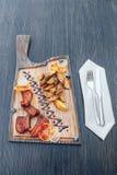 Πικάντικα πλευρά χοιρινού κρέατος σχαρών που εξυπηρετούνται με τις τηγανιτές πατάτες σε έναν τέμνοντα πίνακα στοκ φωτογραφία με δικαίωμα ελεύθερης χρήσης