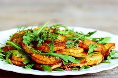 Πικάντικες πατάτες με το arugula σε ένα πιάτο Ψημένες πατάτες με το φρέσκο arugula και το απλό ξηρό μίγμα καρυκευμάτων Στοκ Φωτογραφίες