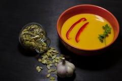 Πικάντικη σούπα κολοκύθας στο σκοτεινό υπόβαθρο στοκ εικόνες