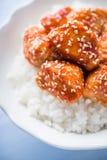 Πικάντικο γλυκόπικρο κοτόπουλο με το σουσάμι και ρύζι στο μπλε ξύλινο υπόβαθρο Στοκ φωτογραφίες με δικαίωμα ελεύθερης χρήσης