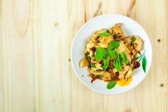 Πικάντικο ταϊλανδικό κοτόπουλο βασιλικού έτοιμο να φάει στο παραδοσιακό πιάτο με το ξύλινο κουτάλι Τοπ όψη Στοκ Εικόνες