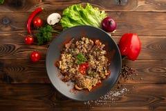 Πικάντικο τηγανισμένο ρύζι με το αρνί στο μαύρο πιάτο στο ξύλινο υπόβαθρο στοκ φωτογραφία με δικαίωμα ελεύθερης χρήσης