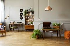Πικάπ και εγκαταστάσεις στον ξύλινο πίνακα στο γκρίζο εσωτερικό διαμερισμάτων με το λαμπτήρα και το βινύλιο Πραγματική φωτογραφία στοκ φωτογραφίες