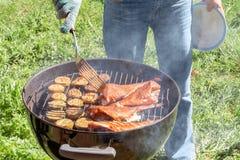 Πικ-νίκ υπαίθρια το καλοκαίρι Μαγείρεμα σε μια στρογγυλή πέρκα θάλασσας ψαριών σχαρών και τις φέτες κολοκυθιών στοκ εικόνα με δικαίωμα ελεύθερης χρήσης