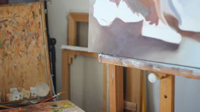 Πινέλα στο υπόβαθρο εργαστηρίων τέχνης Υλικός στενός επάνω ελαιογραφίας pan Κέρδος της βούρτσας χρωμάτων με την παλέτα φιλμ μικρού μήκους