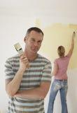 Πινέλο εκμετάλλευσης ανδρών ενώ η γυναίκα χρωματίζει τον τοίχο με τον κύλινδρο Στοκ φωτογραφία με δικαίωμα ελεύθερης χρήσης
