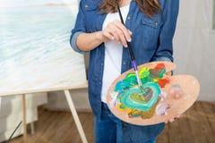 Πινέλο και παλέτα εκμετάλλευσης καλλιτεχνών γυναικών χρωματίζοντας την εικόνα Στοκ Εικόνες