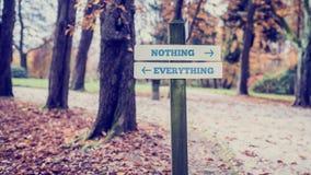Πινακίδα με δύο σημάδια που λένε - τίποτα όλα - που δείχνουν στοκ εικόνα