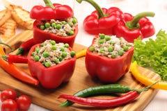 Πιπέρια που γεμίζονται με το ρύζι και τα λαχανικά κρέατος στον τέμνοντα πίνακα Στοκ Φωτογραφία