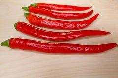 Πιπέρια τσίλι που διαδίδονται έξω σε μια σειρά στον πίνακα Στοκ Φωτογραφίες