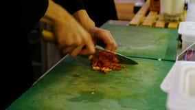 Πιπέρι μαγείρων αρχιμαγείρων cutts επαγγελματικά με ένα μαχαίρι αρχιμαγείρων στον τέμνοντα πίνακα απόθεμα βίντεο