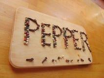 Πιπέρι που γράφεται στον τέμνοντα πίνακα με το πιπέρι Στοκ Φωτογραφία