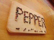 Πιπέρι που γράφεται στον τέμνοντα πίνακα με το πιπέρι Στοκ Φωτογραφίες