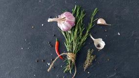 Πιπέρι της Rosemary, σκόρδου και τσίλι στην επιφάνεια πετρών απόθεμα βίντεο