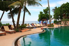 Πισίνα άποψης θάλασσας, αργόσχολοι ήλιων δίπλα στον κήπο και την παραλία του ωκεανού στοκ φωτογραφία