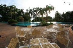 Πισίνα, αργόσχολοι ήλιων δίπλα στον κήπο και κτήρια στοκ φωτογραφίες με δικαίωμα ελεύθερης χρήσης