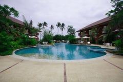 Πισίνα, αργόσχολοι ήλιων δίπλα στον κήπο και κτήρια στοκ φωτογραφία με δικαίωμα ελεύθερης χρήσης
