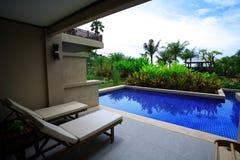 Πισίνα, αργόσχολοι ήλιων δίπλα στον κήπο και κτήρια στοκ φωτογραφία
