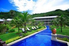 Πισίνα, αργόσχολοι ήλιων δίπλα στον κήπο και κτήρια στοκ εικόνα