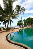 Πισίνα, αργόσχολοι ήλιων δίπλα στον κήπο και τον ωκεάνιο ορίζοντα στοκ φωτογραφία