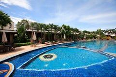 Πισίνα, αργόσχολοι ήλιων δίπλα στον κήπο και το μπανγκαλόου στοκ εικόνα
