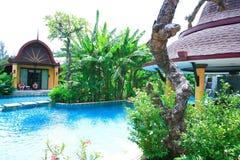 Πισίνα, αργόσχολοι ήλιων δίπλα στον κήπο και το μπανγκαλόου στοκ εικόνες