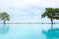 Πισίνα με το δέντρο Plumeria και το μπλε ουρανό και τον ωκεανό Στοκ φωτογραφία με δικαίωμα ελεύθερης χρήσης