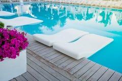 Πισίνα με το μόνιππο -μόνιππο-longue στο νερό Στοκ εικόνες με δικαίωμα ελεύθερης χρήσης