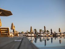 Πισίνα του ξενοδοχείου διακοπών πολυτέλειας, καταπληκτική άποψη Χαλαρώστε κοντά στη λίμνη με το κιγκλίδωμα, sunbeds, τους αργοσχό στοκ φωτογραφίες με δικαίωμα ελεύθερης χρήσης