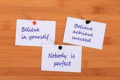 Πιστεψτε σε σας Θεωρήστε ότι επιτύχετε πετυχαίνει Κανένας δεν είναι τέλειος Καρφίτσα σημειώσεων στον πίνακα δελτίων Στοκ Εικόνα