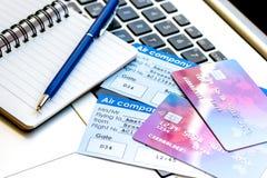 Πιστωτικές κάρτες με τα εισιτήρια αερογραμμών για τις διακοπές στο υπόβαθρο lap-top Στοκ Εικόνες