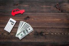 Πιστωτική έννοια αυτοκινήτων Τα χρήματα και ο υπολογιστής κοντά στο αυτοκίνητο σκιαγραφούν στο σκοτεινό ξύλινο υπόβαθρο το τοπ δι Στοκ εικόνα με δικαίωμα ελεύθερης χρήσης