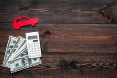 Πιστωτική έννοια αυτοκινήτων Τα χρήματα και ο υπολογιστής κοντά στο αυτοκίνητο σκιαγραφούν στο σκοτεινό ξύλινο υπόβαθρο το τοπ δι Στοκ φωτογραφίες με δικαίωμα ελεύθερης χρήσης