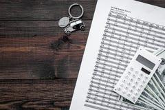 Πιστωτική έννοια αυτοκινήτων Χρήματα και υπολογιστής keychain πλησίον στη μορφή της σκιαγραφίας αυτοκινήτων στη σκοτεινή ξύλινη τ Στοκ φωτογραφίες με δικαίωμα ελεύθερης χρήσης