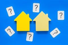 Πιστωτική έννοια υποθηκών με το παιχνίδι σπιτιών και ερωτηματικό στην μπλε τοπ άποψη υποβάθρου στοκ εικόνες