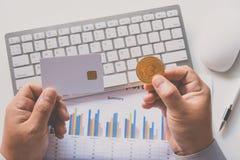 Πιστωτική κάρτα εκμετάλλευσης χεριών με τα bitcoins με ένα υπόβαθρο lap-top Στοκ Εικόνες