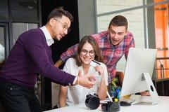 Πιστωτική κάρτα λαβής Διαδικτύου ρολογιών τριών νέα επιχειρηματιών Στοκ Εικόνες