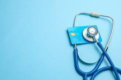 Πιστωτική κάρτα με το στηθοσκόπιο στο μπλε υπόβαθρο Η έννοια του ιατρικού strechevka ή της ακριβής ιατρικής, μισθός γιατρών αντίγ στοκ φωτογραφίες με δικαίωμα ελεύθερης χρήσης